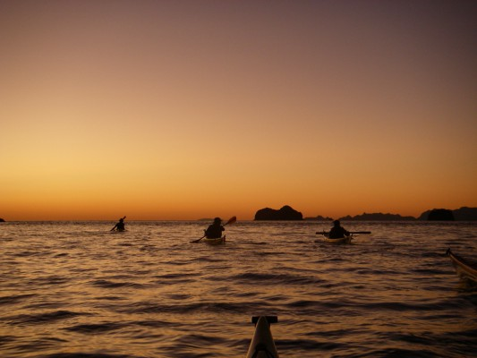 4 kayakers paddling into the sunrise