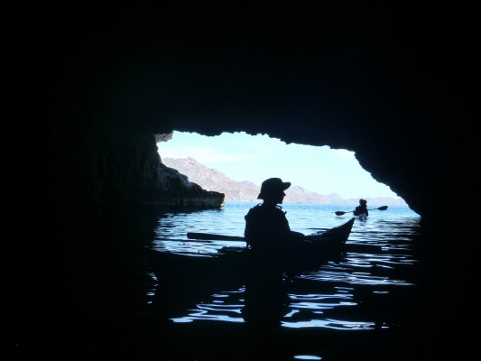 Kayaker silhouetted inside a cave