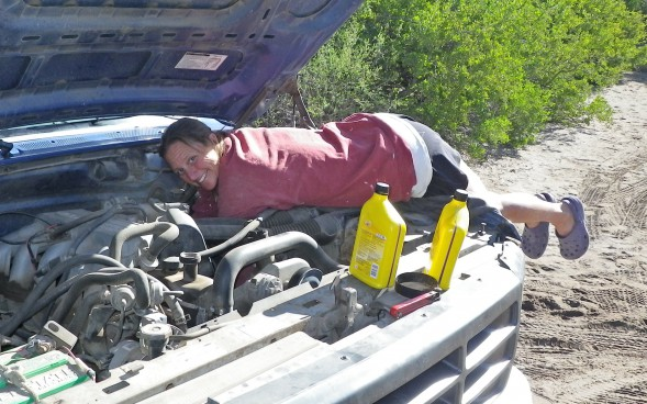 Ginni changing the oil in the Blue Ford.