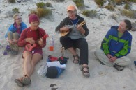 2 ukeleles and 4 singers in the sand