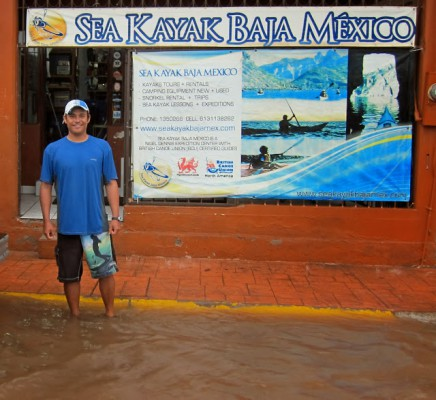 Ramon stands ankle deep in rain outside the Sea Kayak Baja Mexico retail store in Loreto, BCS