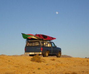 Desert Road with blue truck with kayaks on roof.